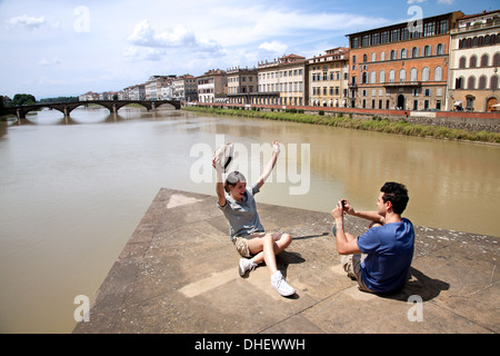 Man photographing woman with Ponte alle Grazie in background, Florence, Tuscany, Italy - Stock Photo
