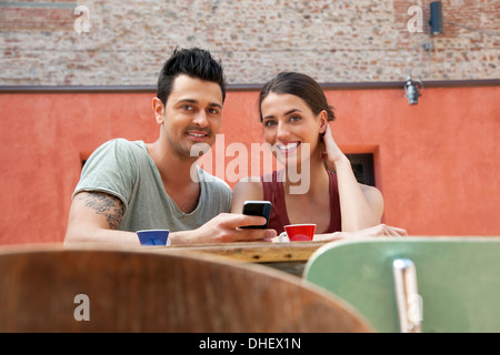 Couple with smartphone outside cafe, Florence, Tuscany, Italy - Stock Photo