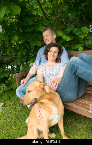 Mature couple sitting on garden bench with dog - Stock Photo