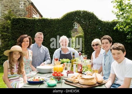 Portrait of three generational family enjoying lunch outdoors - Stock Photo