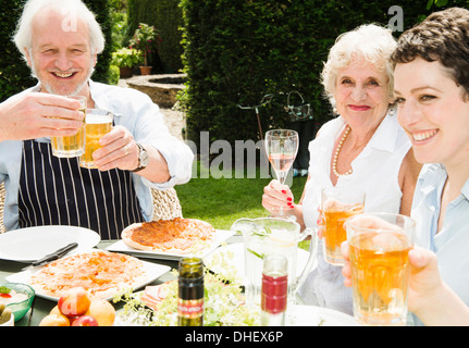 Group of people enjoying food and drink outdoors - Stock Photo
