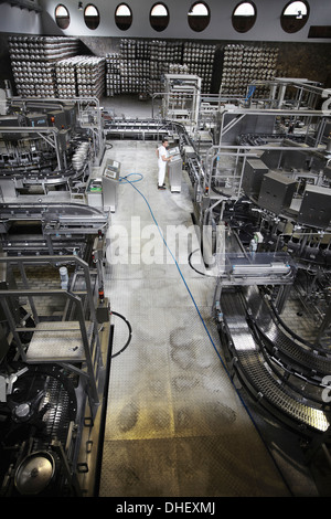 Worker and machinery in a brewery - Stock Photo