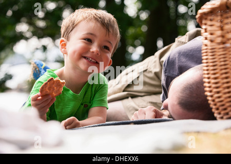 Boy enjoying picnic with father - Stock Photo