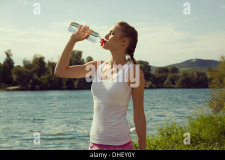 Young female jogger drinking bottled water - Stock Photo