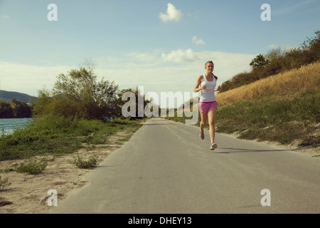Young female jogger running along riverside - Stock Photo
