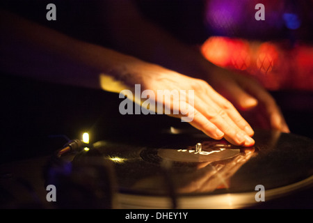 Close up of DJ's hands spinning vinyl in nightclub - Stock Photo