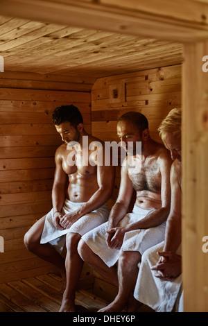 Three men sitting in sauna with heads down - Stock Photo