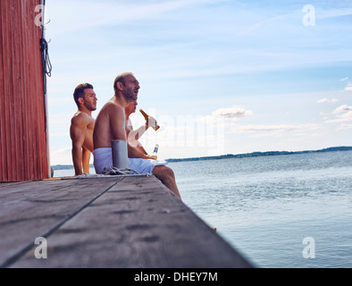 Three male friends sitting outside sauna enjoying beer - Stock Photo