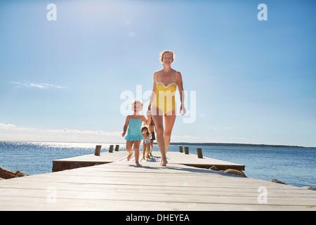 Family walking on jetty, Utvalnas, Gavle, Sweden - Stock Photo