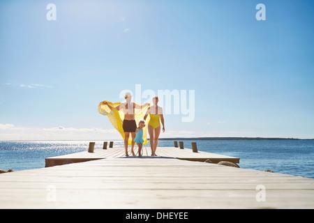 Female toddler and parents on pier, Utvalnas, Gavle, Sweden - Stock Photo