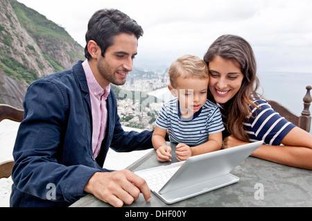 Young family with laptop, Casa Alto Vidigal, Rio De Janeiro, Brazil - Stock Photo