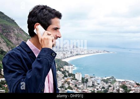 Young man using mobile phone, Casa Alto Vidigal, Rio De Janeiro, Brazil - Stock Photo