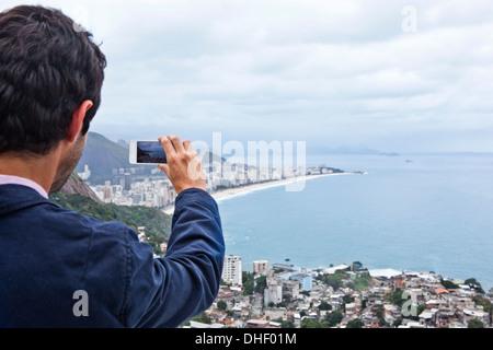 Young man photographing with mobile phone, Casa Alto Vidigal, Rio De Janeiro, Brazil - Stock Photo