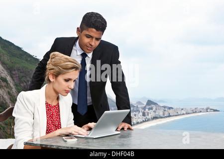 Young couple using laptop, Casa Alto Vidigal, Rio De Janeiro, Brazil - Stock Photo
