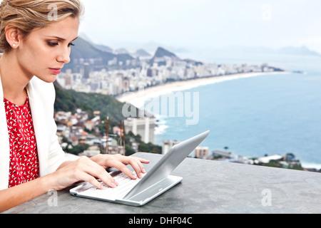 Young woman using laptop, Casa Alto Vidigal, Rio De Janeiro, Brazil - Stock Photo
