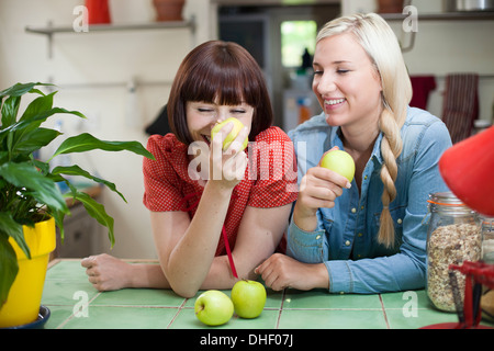 Female friends in kitchen with apples - Stock Photo