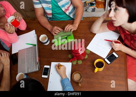 Flatmates brainstorming around kitchen table - Stock Photo