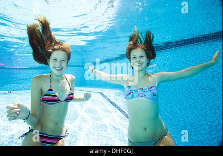 Two teenage girls swimming underwater in swimming pool - Stock Photo
