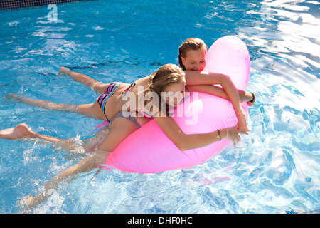 Two teenage girls holding onto air bed in swimming pool - Stock Photo