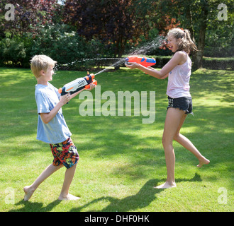 Brother and sister play fighting with water guns in garden - Stock Photo