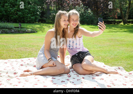 Two teenage girls on picnic blanket taking self portrait - Stock Photo