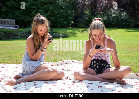Two teenage girls on picnic blanket looking at mobile phones - Stock Photo