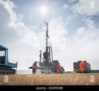 Workers and drilling rig exploring for coal in field - Stock Photo