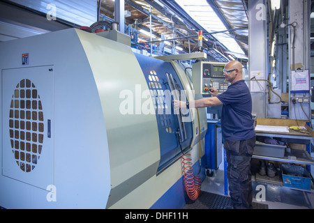 Engineer using computer numerical controlled (CNC) lathe in factory - Stock Photo