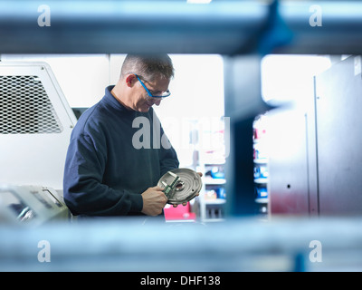 Engineer measuring metal part in factory - Stock Photo