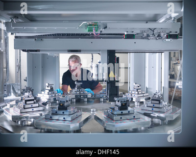 Engineer inspecting automatic lathe in factory - Stock Photo