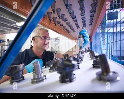 Engineer selecting lathe cutting tools in factory - Stock Photo