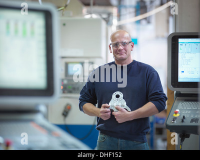 Engineer holding complex metal component in factory, portrait - Stock Photo