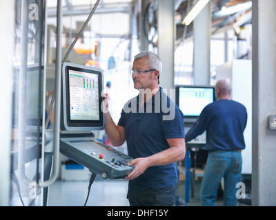 Engineers at lathe controls in factory - Stock Photo