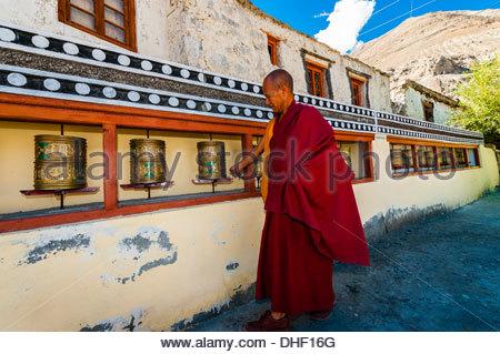 A monk turns prayer wheels at he circumambulates around the Diskit Monastery, Nubra Valley, Ladakh, Jammu and Kashmir - Stock Photo