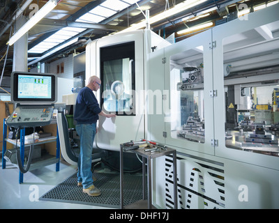 Engineer at computer numerical controlled lathe (CNC) in factory - Stock Photo