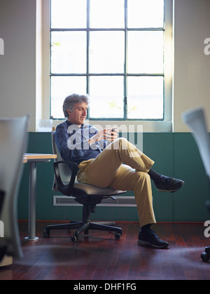 Mature businessman sitting on office chair wit cell phone - Stock Photo