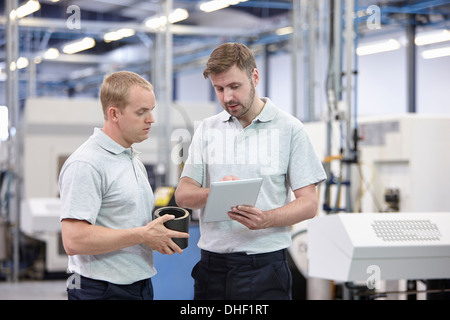 Two workers looking at digital tablet in engineering warehouse - Stock Photo