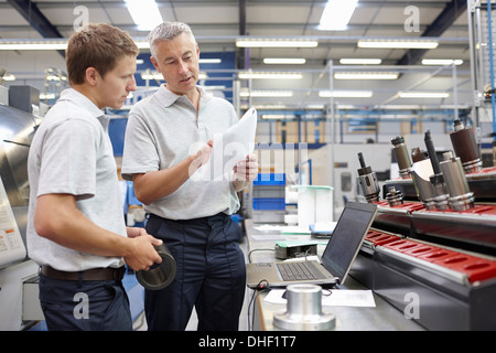 Worker and manager meeting in engineering warehouse - Stock Photo