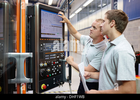 Workers looking at computer monitor in engineering factory - Stock Photo