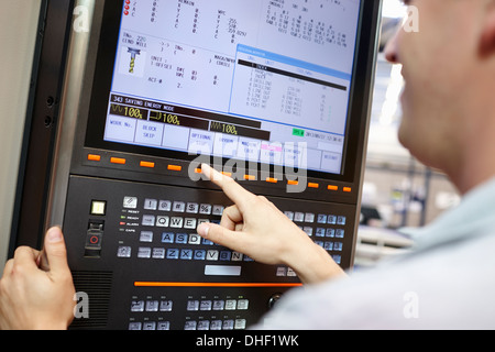 Worker checking computer monitor in engineering factory - Stock Photo