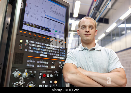 Portrait of engineer and control panel in engineering factory - Stock Photo