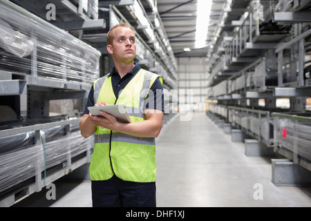 Worker checking order in engineering warehouse - Stock Photo