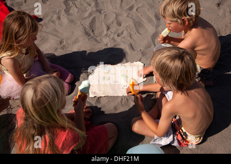 Four friends eating ice creams on beach, high angle, Wales, UK - Stock Photo