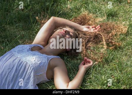 Teenage girl lying on grass, Prague, Czech Republic - Stock Photo