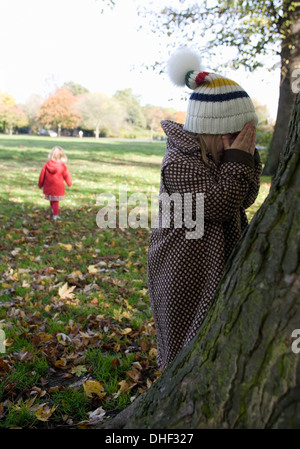 Girls playing hide and seek in park, London, England, UK - Stock Photo
