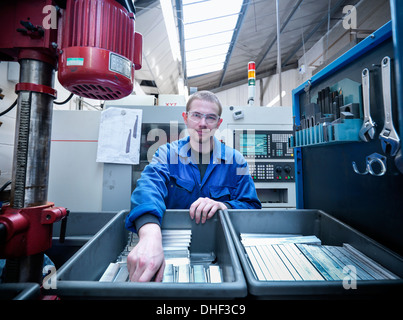 Apprentice engineer with components in factory, portrait - Stock Photo
