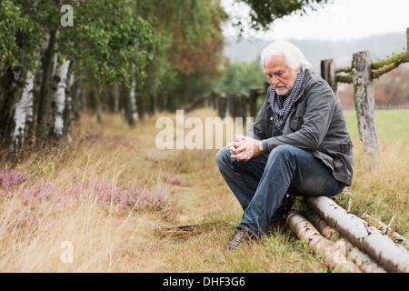 Senior man sitting on log - Stock Photo