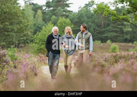 Senior man, mid adult man and woman walking through forest - Stock Photo