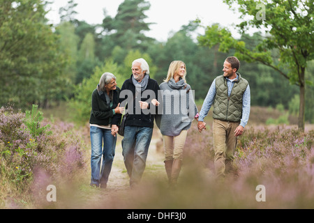 Two couples walking through forest - Stock Photo
