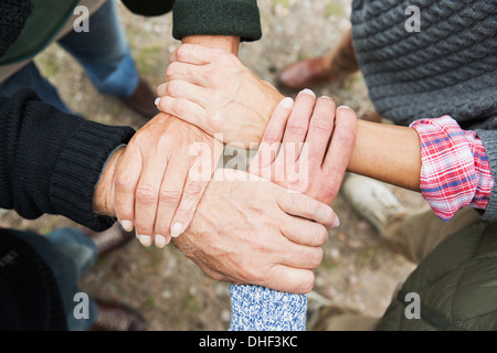Four people touching hands, high angle - Stock Photo
